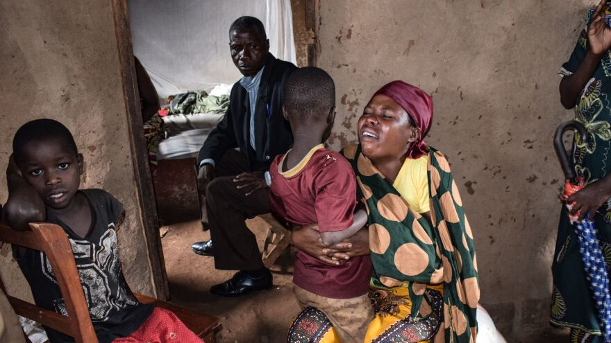 Family members of victims killed by an armed group mourn in the village of Ruhagarika on Saturday, where 26 people were killed, in northwestern Burundi.
