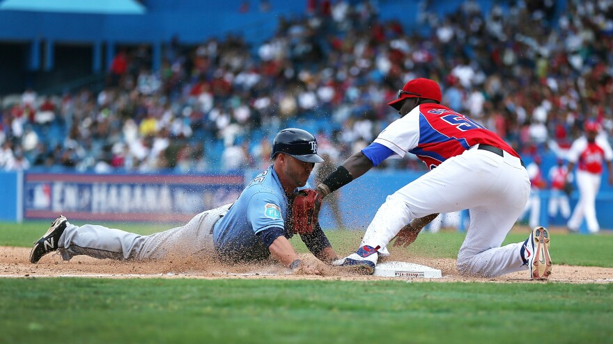 Tampa Bay Rays' Steve Pearce dives safely into third base during an exhibition game between the Cuban national team and the Tampa Bay Rays at the Estado Latinoamericano March 22, 2016 in Havana, Cuba.