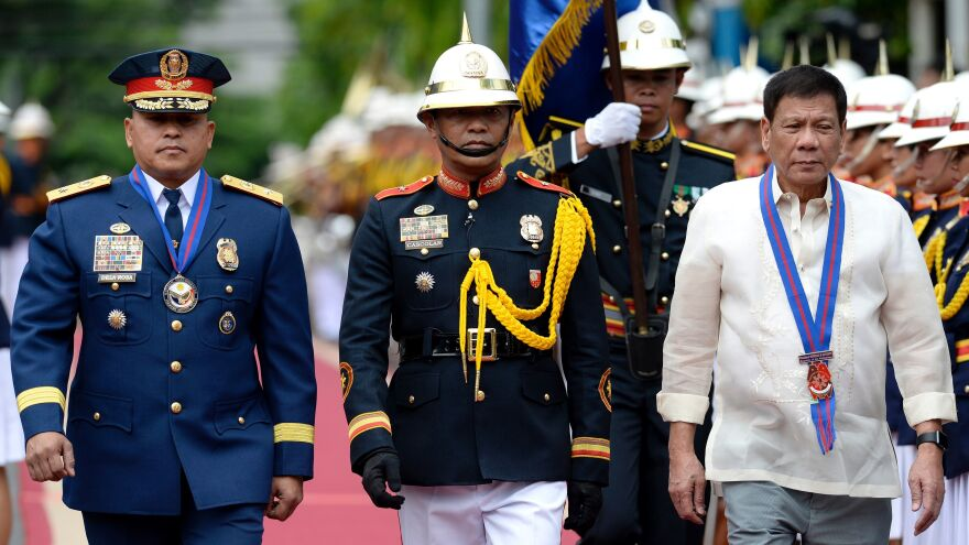 The new president of the Philippines, Rodrigo Duterte (right) walks beside the new police chief, Ronald Bato Dela Rosa, (left) as he was sworn in on July 1 in Manila. Duterte assumed the presidency on June 30, pledging a ruthless approach to suspected drug traffickers. Dozens have been killed by police in recent days.