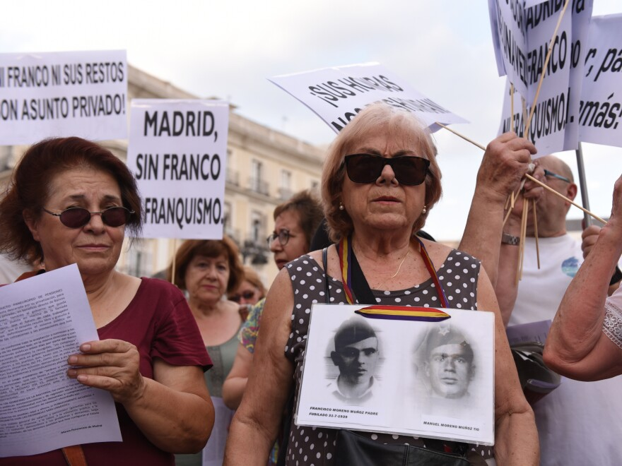 A protester holds pictures of people who went missing during the Spanish dictatorship of Francisco Franco from 1936-1975. Protesters in Madrid this summer demand the exhumation of Franco from Valley of the Fallen.