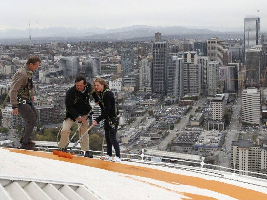 """Jeff Wright (center), whose family owns the Space Needle, starts the repainting of the iconic structure on Tuesday with his 15-year-old daughter, Mauren, and Space Needle board member Stuart Rolfe. The new color is the original color, dubbed """"galaxy gold."""""""