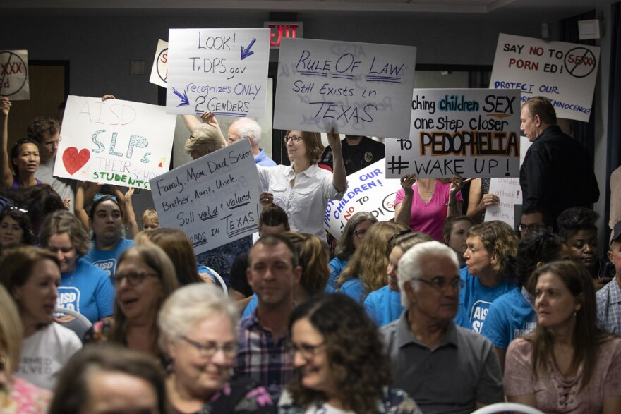 Residents hold signs during an AISD school board meeting