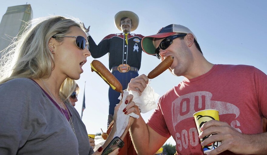 Gwin and Ryan Huey eat corny dogs in front of Big Tex at the State Fair of Texas before the annual Red River Showdown college football game between Texas and Oklahoma. Almost 80 years after the corny dog's debut, it's a traditional Fair snack.