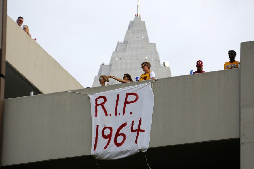 Cleveland fans hang a sign from a parking garage across from the Quicken Loans Arena early Wednesday before the parade.