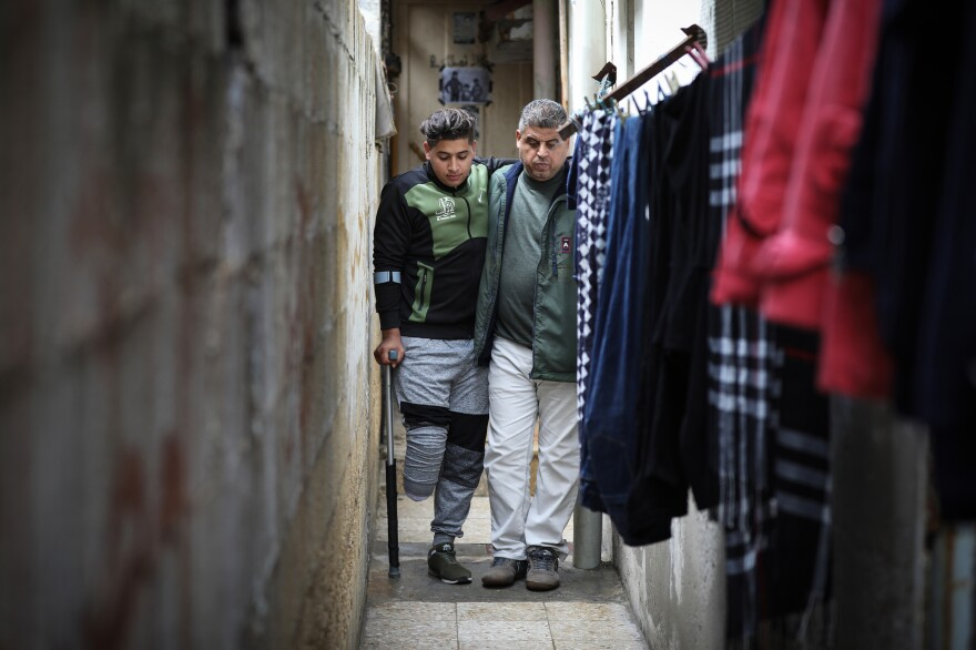 Hisham Abu Ghaben walks with his son, Mohammed, between alleys near their home in Gaza City. Mohammed, 18, was one of more than 100 young Palestinians with a leg amputated after being shot by Israeli troops at Gaza border protests.