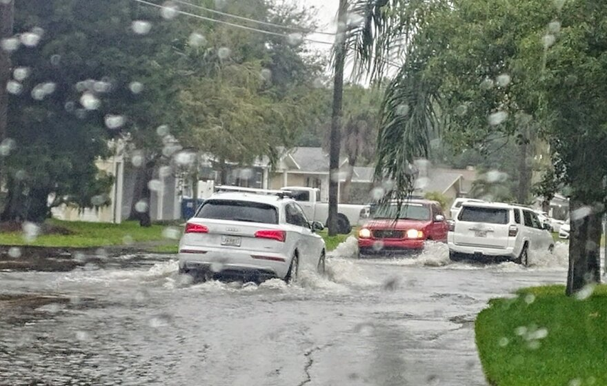 Cars driving through Shore Acres street flooding