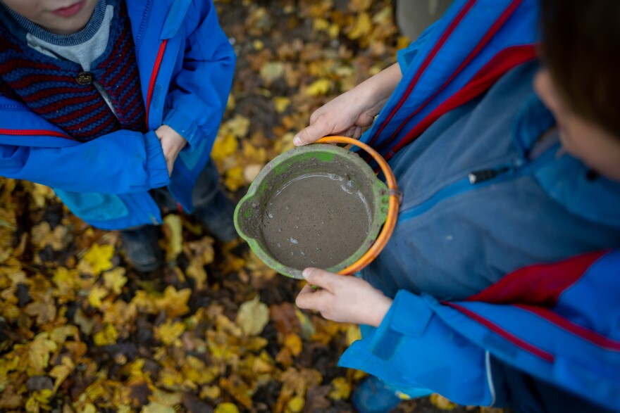A child holds a bucket of mud while at the Kallemach Waldkindergarten, a forest preschool in a sprawling park in Munich, Germany, on Nov. 3, 2020.
