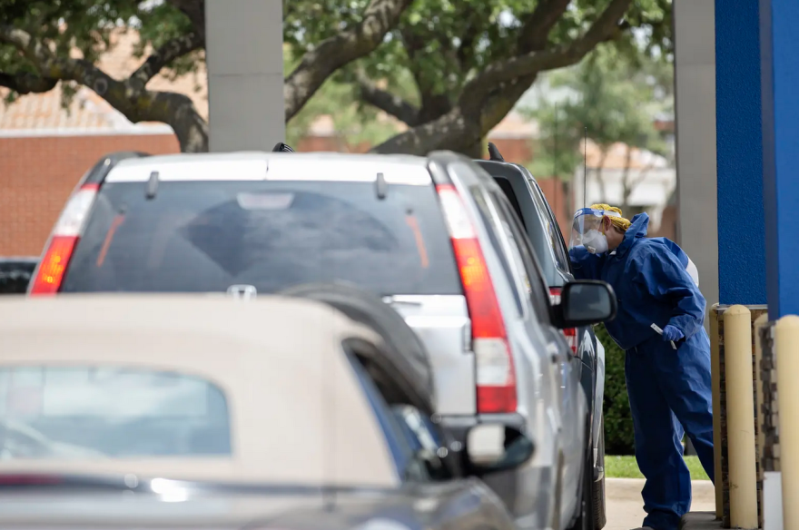 A health care worker administers a coronavirus test on a patient at a drive thru testing site at Exceptional Medical Plaza in Garland on June 30.