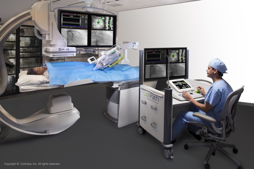 A surgeon sits behind a console and uses a joystick to manipulate robotic arms during a surgery.