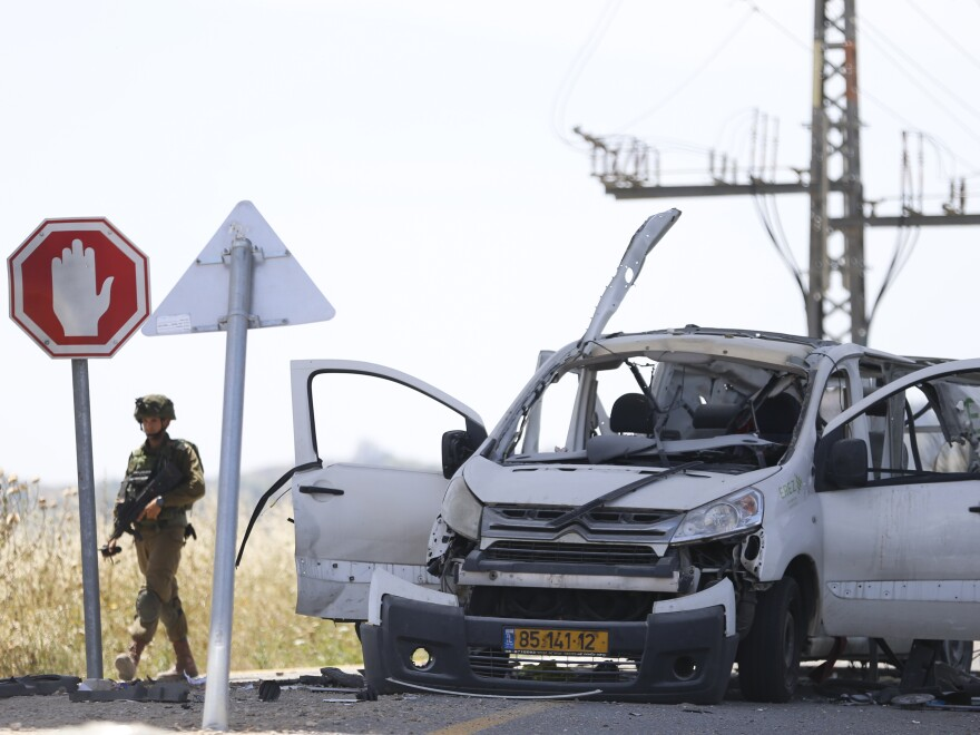 Israeli soldier walks past a car hit by a missile fired from Gaza near the Gaza and Israel border on Sunday.