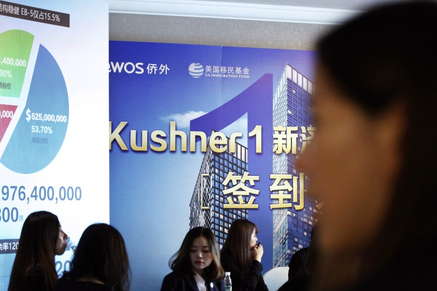 Chinese staff wait for investors at a reception desk on Sunday in Shanghai, China, during an event promoting investment in a Kushner Companies development.