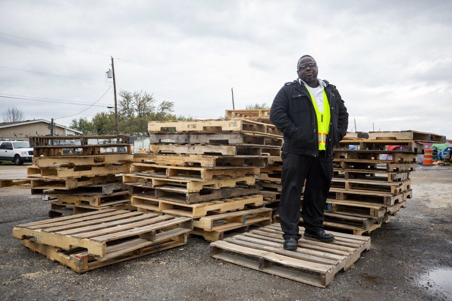 Sean Brinkley, a local pastor, stands with a pile of pallets he donated to the camp.