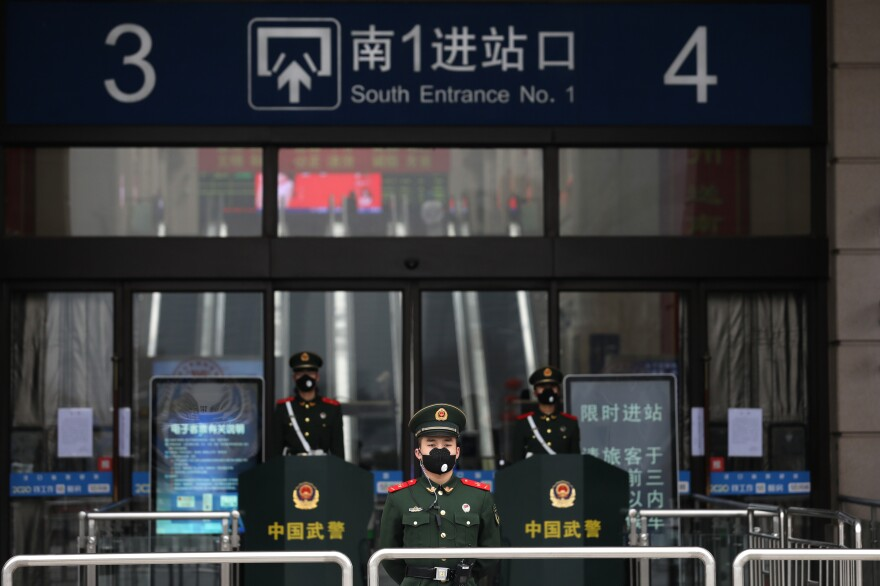 Paramilitary policemen guard the outside of the closed Hankou railway station in Wuhan, China.