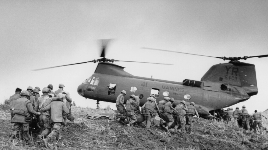 U.S. Marines carry their dead and wounded to a waiting helicopter near the western edge of the demilitarized zone in South Vietnam on June 21, 1968.