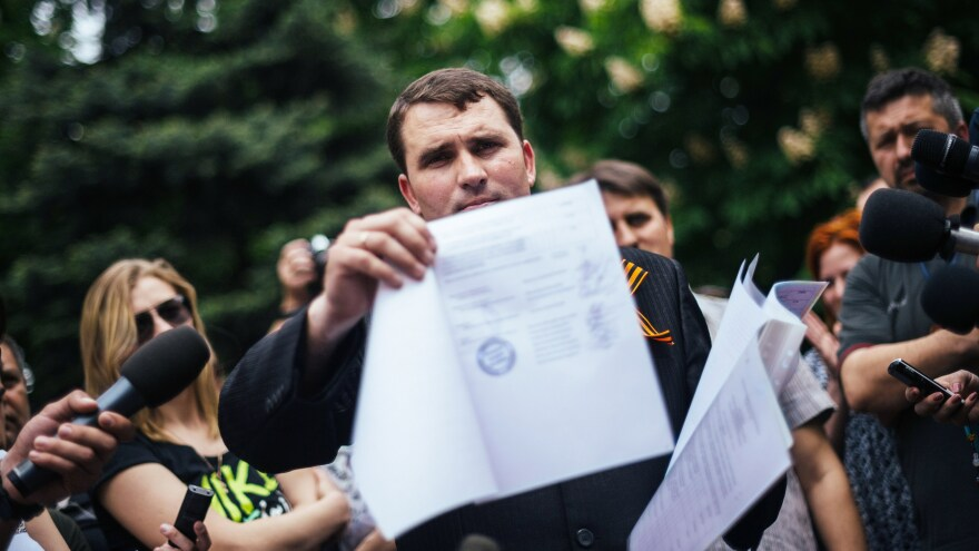 """In the eastern Ukrainian city of Lugansk, the """"chairman of the Central Election Commission"""" Alexander Malykhin shows a document with the results of a referendum outside the regional state administration building Monday. He said voters had chosen to leave Ukraine."""
