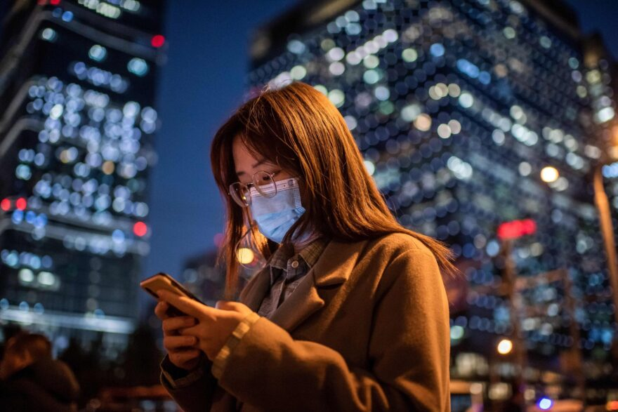 A woman wearing a face mask looks at her cellphone in Beijing, China.
