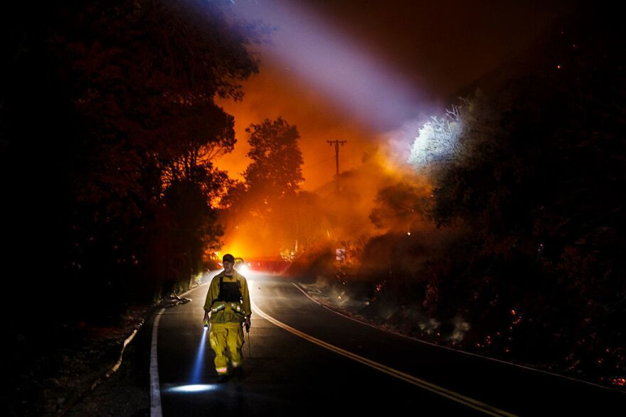 A firefighter point their beam lights around a burnt area to check for damages made by the Blue Cut fire.