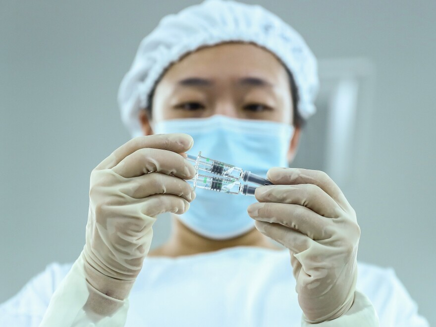 A staff member checks a COVID-19 vaccine package in Beijing. China has approved Sinopharm's vaccine, after clinical trials showed the drug has a 79.34% efficacy against COVID-19.