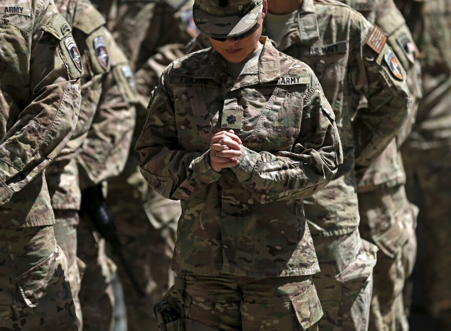 A U.S. soldier prays during a ceremony marking the 14th anniversary of the 9/11 attacks on the United States, in Kabul, Afghanistan September 11, 2015.