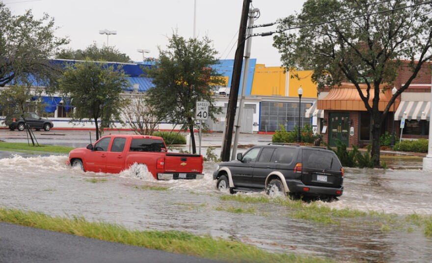Cars travel through floodwaters in Houston. Often, flood damaged cars can end up in used car lots.