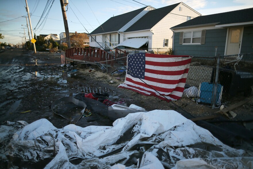 An American flag flies in front of a home damaged by Superstorm Sandy on Nov. 1, 2012, in Toms River, N.J.