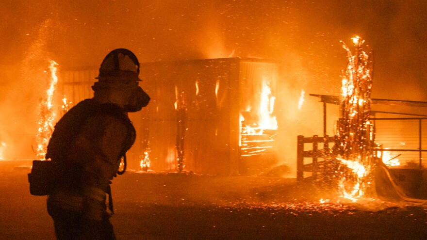Firefighters look on as a blaze tears through structures on a farm Sunday in Windsor, Calif., where the Kincade Fire has driven residents from their homes.