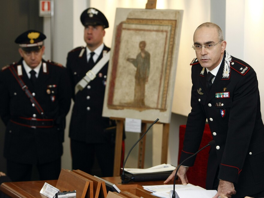 Italian Carabinieri paramilitary police general Giovanni Nistri (right) discusses the recovery and seizure of nearly 60,000 pieces of looted or stolen artwork and archaeological artifacts at a press conference in January 2010. Beside him is one of those pieces, a plaster wall painting dating back some 2,000 years.