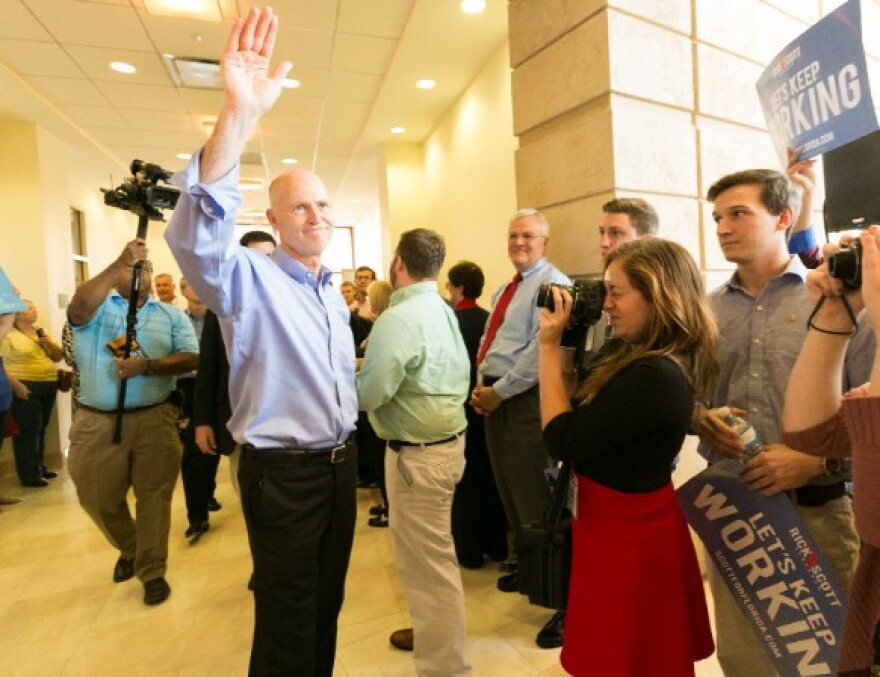 Gov. Rick Scott waves to supporters during a campaign stop last month in Lakeland.