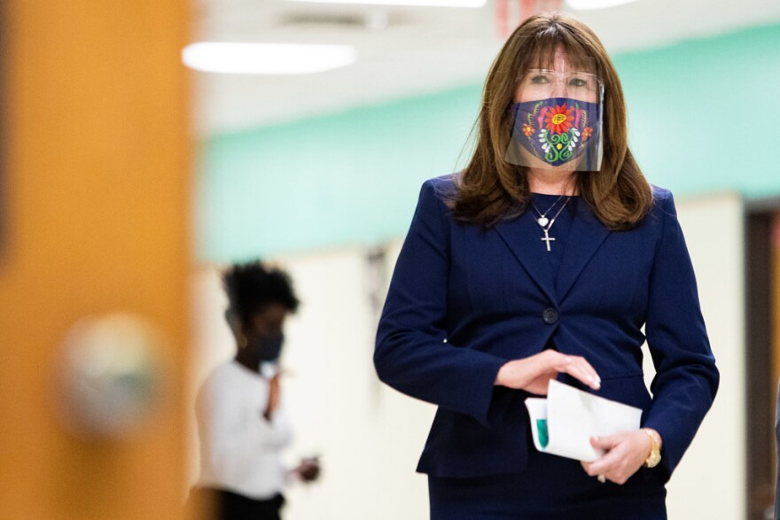 Austin ISD Superintendent Stephanie Elizalde walks down the hallway of LBJ Early College High School wearing a face mask and face shield.