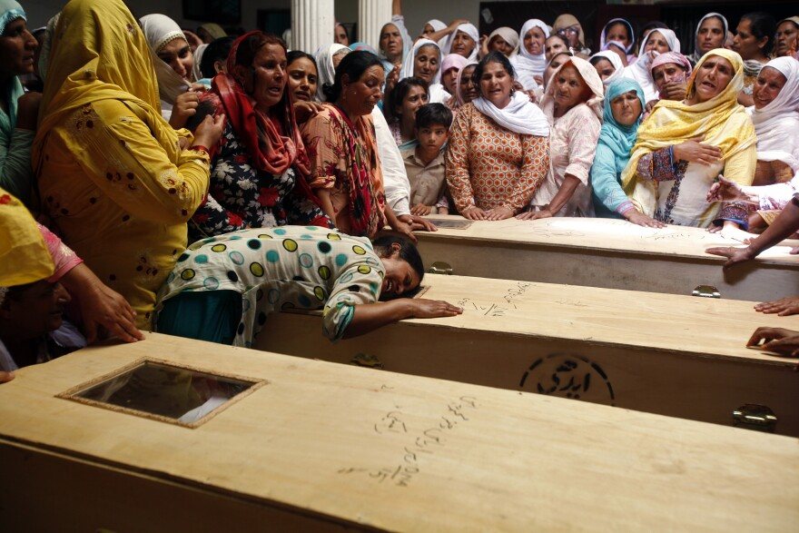 A relative of one of the children who died after a fire on a school bus, cries over the coffin, on the outskirts of Gujrat.