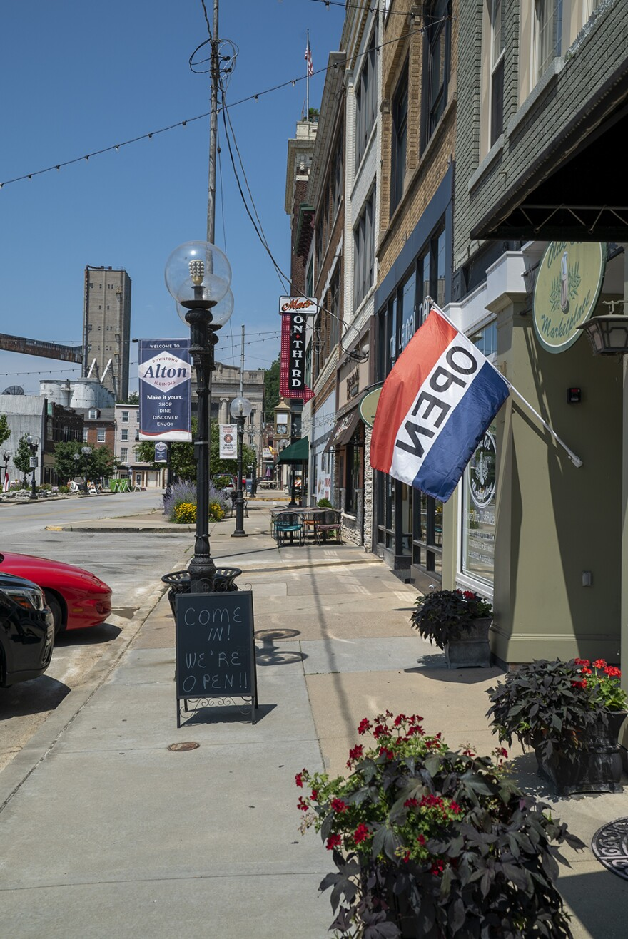 Businesses in downtown Alton display signs and flags indicating they're open on July 2, 2019. Major flooding forced many of them to close for nearly two months in May and June.