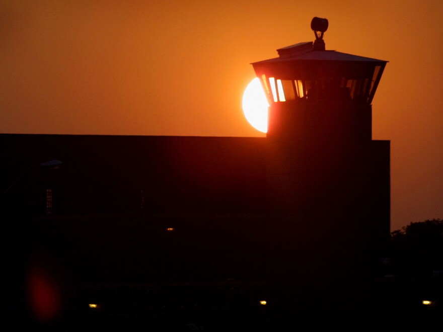 The sun sets behind a guard tower at the federal prison in Terre Haute, Ind.