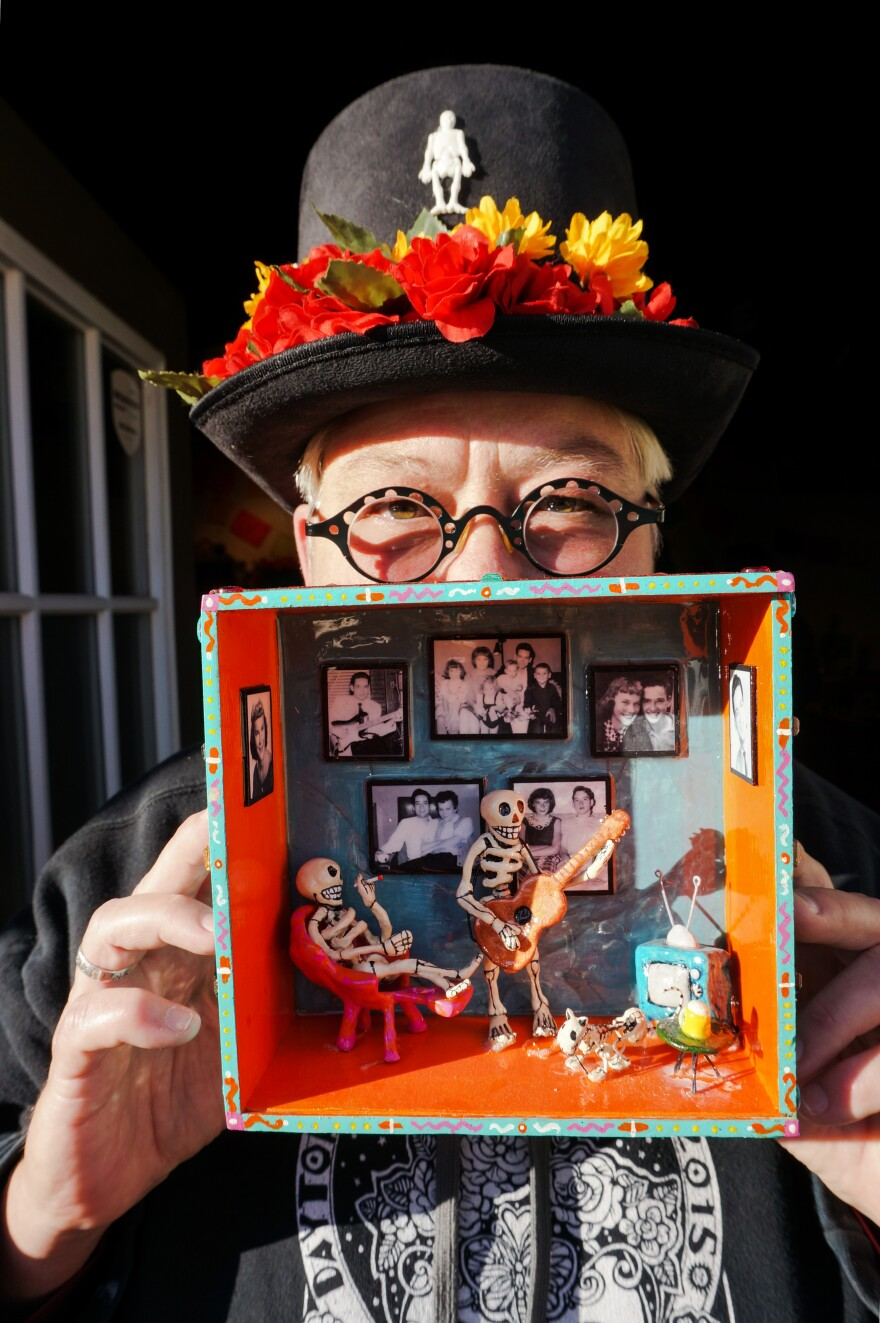Local artist M.B. Hopkins holds up the alter she made inside a cigar box for her mother and father (and their cat).