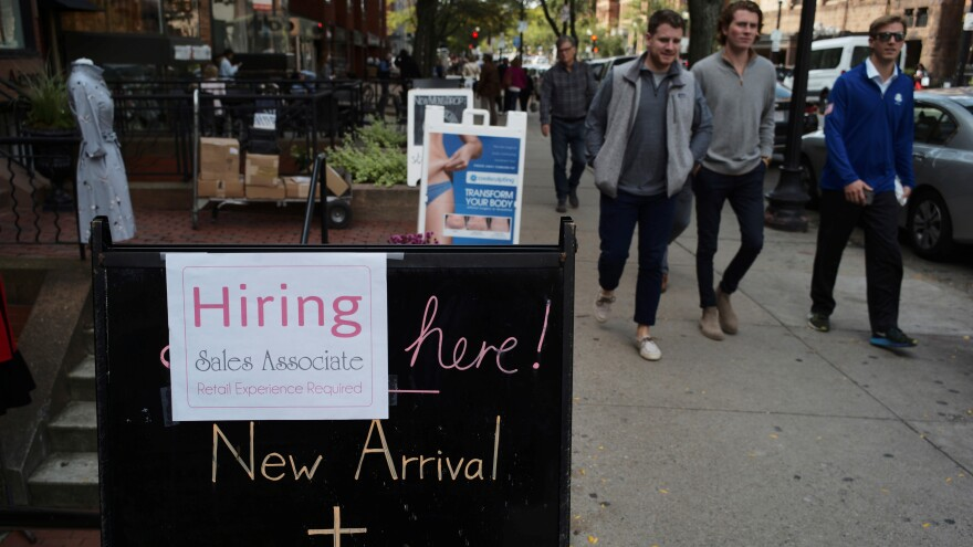 Retail jobs have taken a hit, losing 67,000 jobs in 2017 after seeing a large gain the year before. In this photo from October, people pass a sign advertising a sale and a job at a shop in Boston last fall.