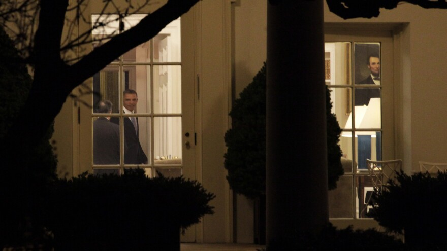 """President Obama was in the Oval Office late Tuesday night as the House finished voting on the """"fiscal cliff"""" deal. After praising the passage, he left for Hawaii to resume a vacation with his family."""