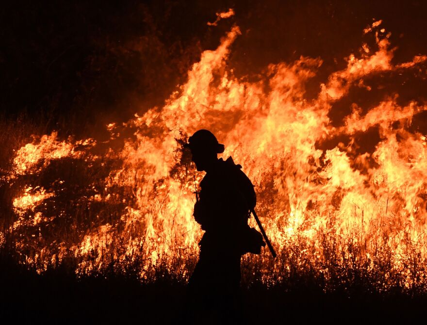 Firefighters conduct a controlled burn to defend houses against flames from the Ranch Fire, as it continues to spread toward the town of Upper Lake, Calif., last week.