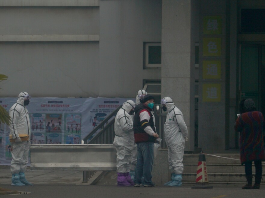 Staff in biohazard suits hold a metal stretcher on Tuesday by the inpatient department of Wuhan Medical Treatment Center, where some people infected with a novel coronavirus are being treated in China.