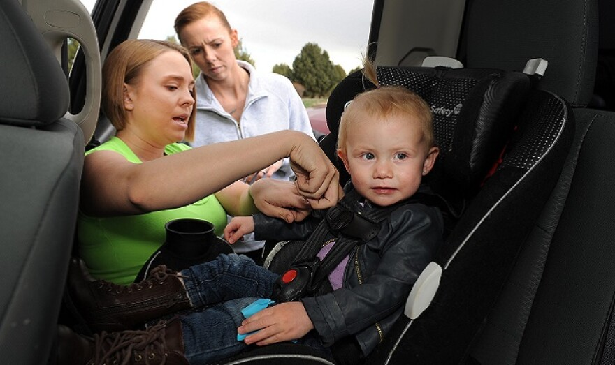 Air Force Staff Sgt. Ashley Sandoval (left), 21st Force Support Squadron, secures Savannah Butler (right) into her car seat as Savannah's mother, Air Force Staff Sgt. Montie Butler (center) looks on.