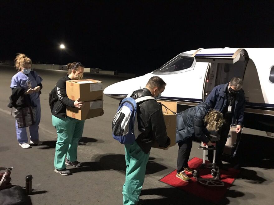 Nurses in scrubs carry boxes to a small jet plane on the tarmac. It's dark out.