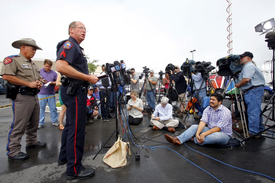 Sgt. Patrick Swanton of the Waco Police Department speaks to the media as Texas Department of Public Safety Trooper D.L. Wilson (left) stands near a Twin Peaks restaurant where nine members of a motorcycle gang were shot and killed in Waco, Texas, on Tuesday.