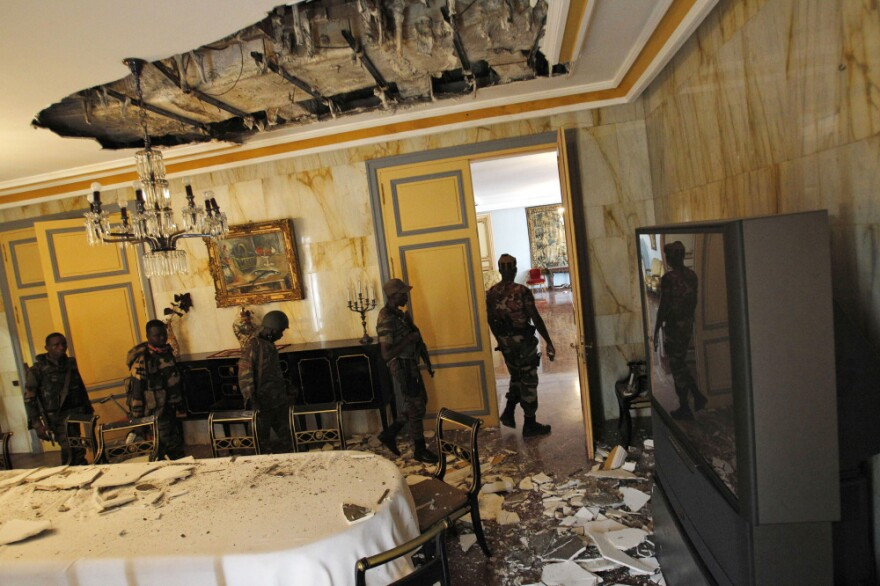 Members of the newly named Republican Forces walk through a damaged dining room of Ivory Coast's presidential palace in central Abidjan on Thursday.