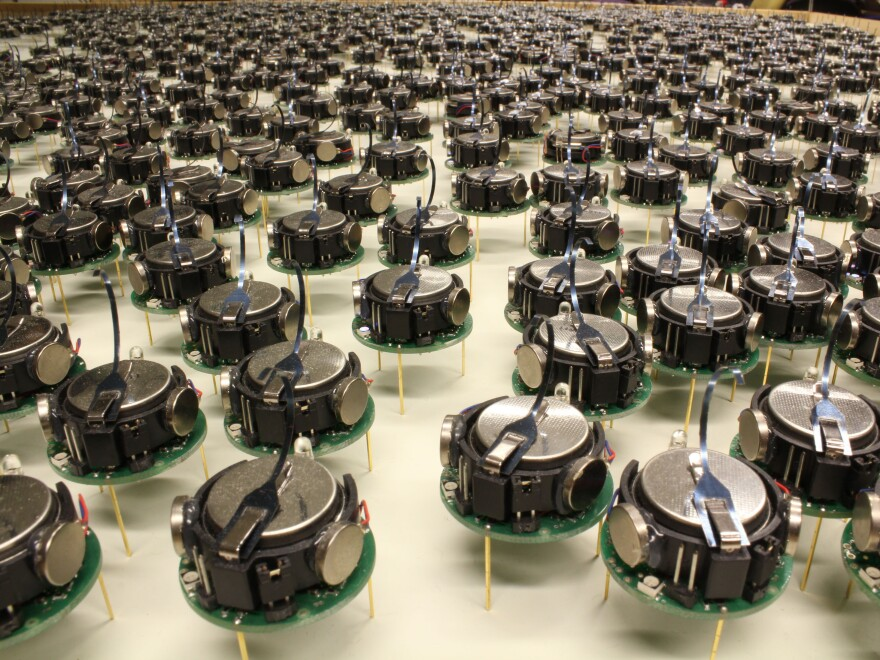 """These 1024 """"kilobots"""" can shuffle into any shape their creator desires. Each robot is a little bigger than a quarter, standing on three little metal legs that vibrate to make it move."""