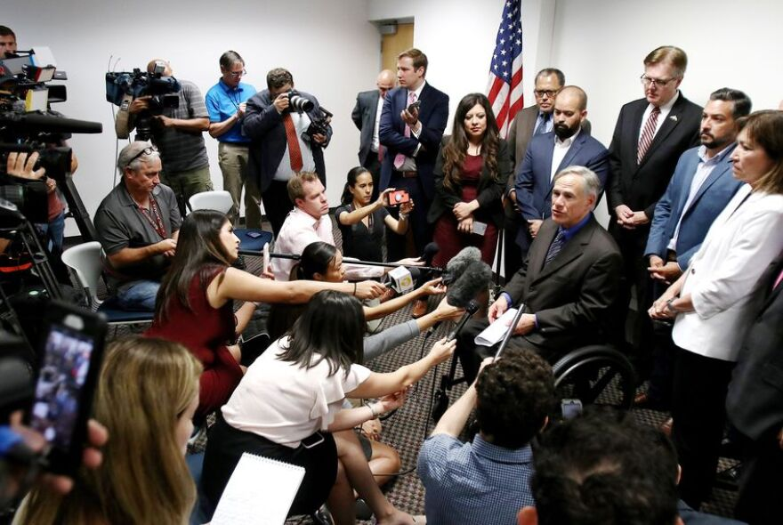 Gov. Greg Abbott surrounded by lawmakers and press