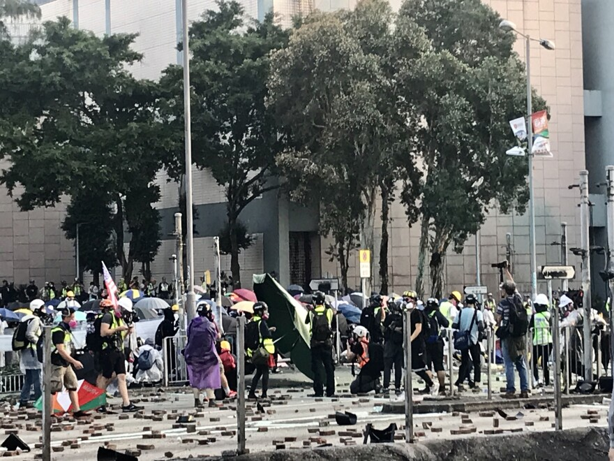 Protesters use umbrellas, bricks, and crude gasoline bombs as they try to hold their position at Polytechnic University.