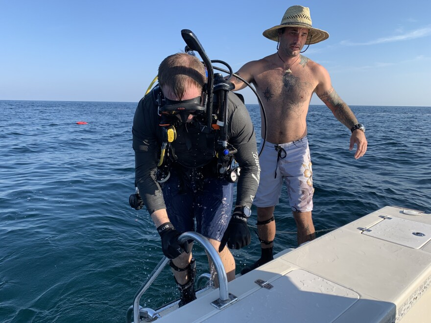 Shawn Campbell helps Justin Herris get back on a boat after completing a dive trip off the coast of Clearwater.