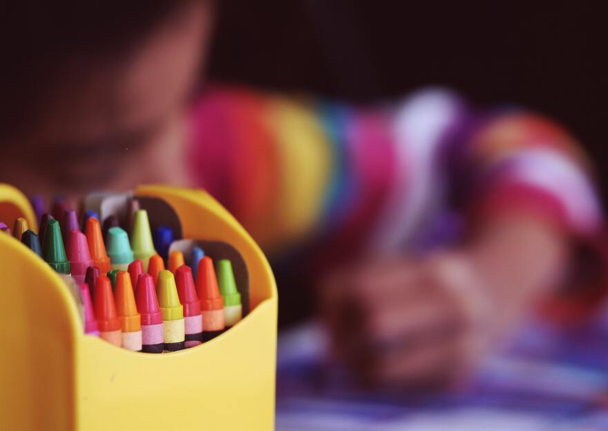 A child draws a picture with crayons.