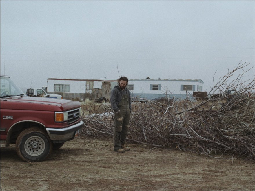 "Photo of the lead actor in ""The Killing of Two Lovers"" film standing outside in front of a red truck and a pile of branches on the ground."