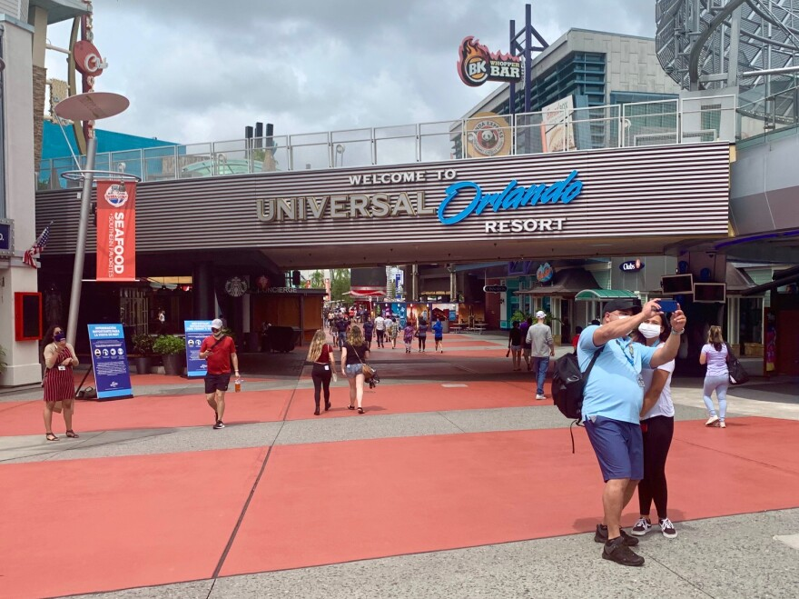 People pose for selfies in front of Universal Orlando entrance sign.