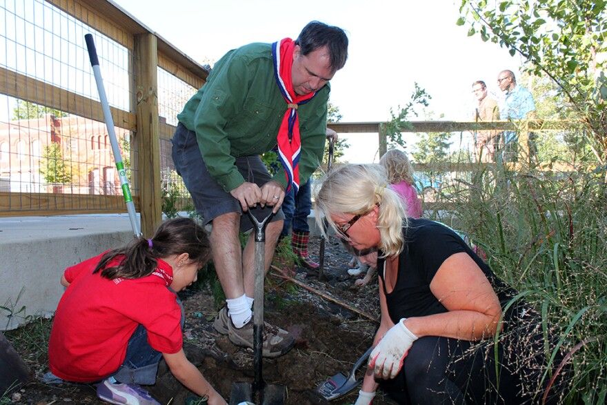 Esme Schumann, (left) Mark Overton and Susie Weinstein dig a hole the City Garden Montessori School in order to plant a new birch tree. In the background, Michael Powers and Aldermanic President Lewis Reed approach.