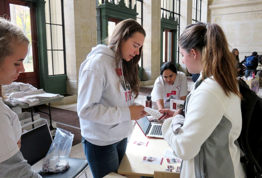"""MIT student activist Larkin Sayre (center) works a booth representing the """"It's on Us"""" campaign in a lobby on campus."""